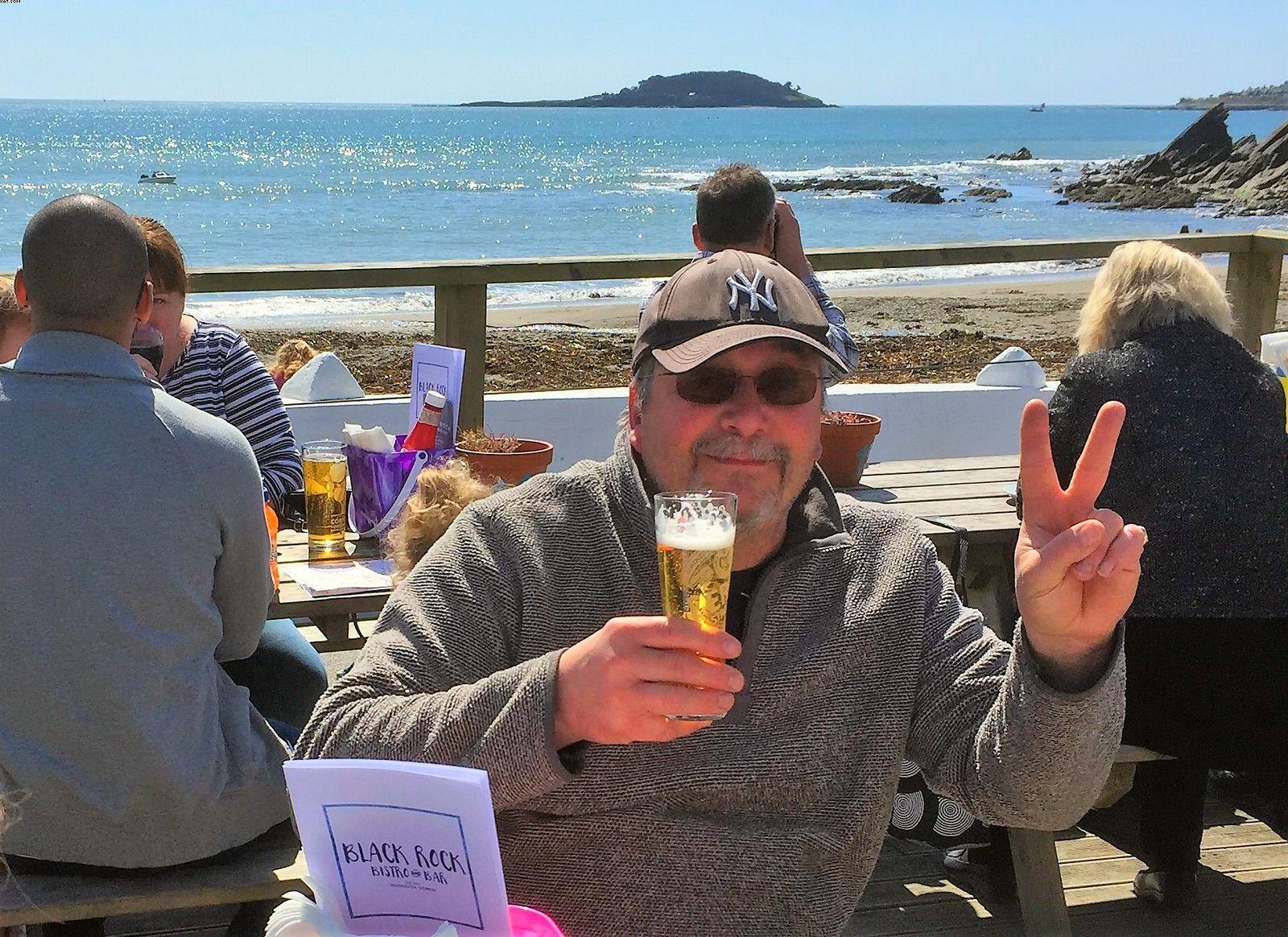 Man enjoying a pint by the sea at Black Rock Cafe near Looe Cornwall