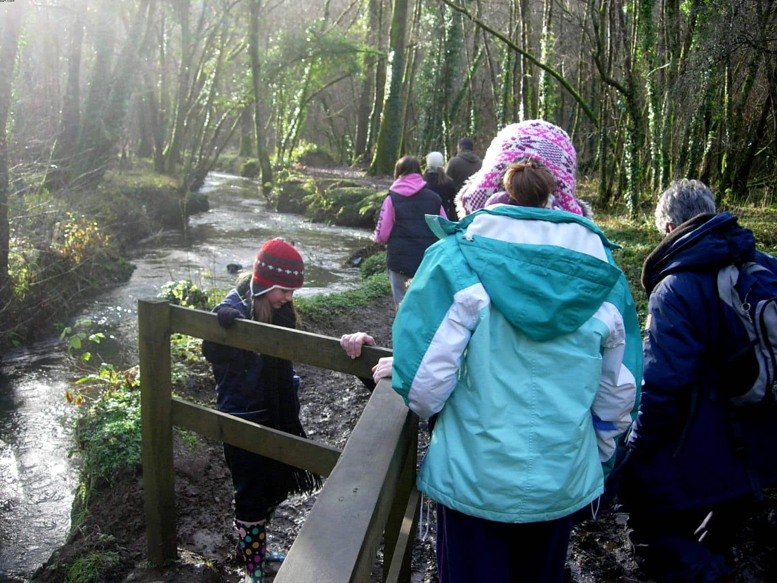 Family walking next to river in Seaton Valley Country Park Cornwall
