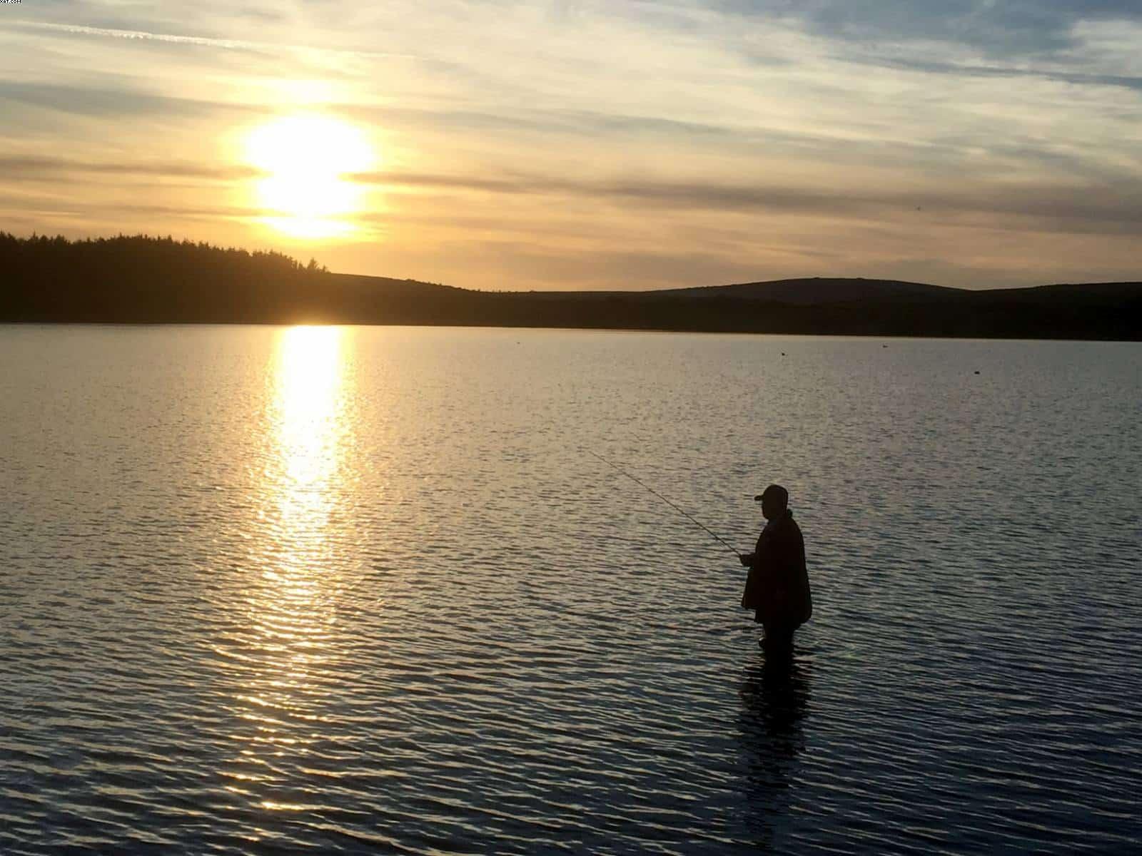 Man fishing at sunset at Siblyback Lake Bodmin Moor