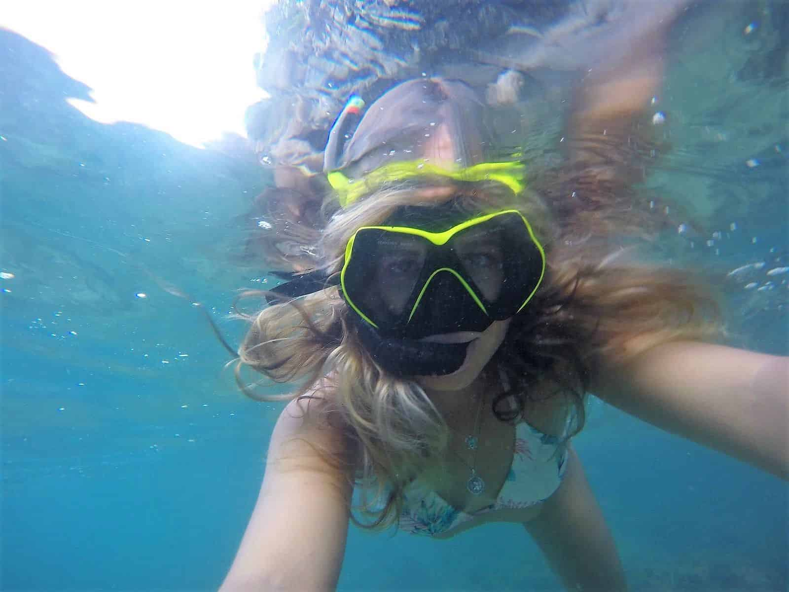 Girl snorkelling in clear water at Hannafore Beach in Looe Cornwall